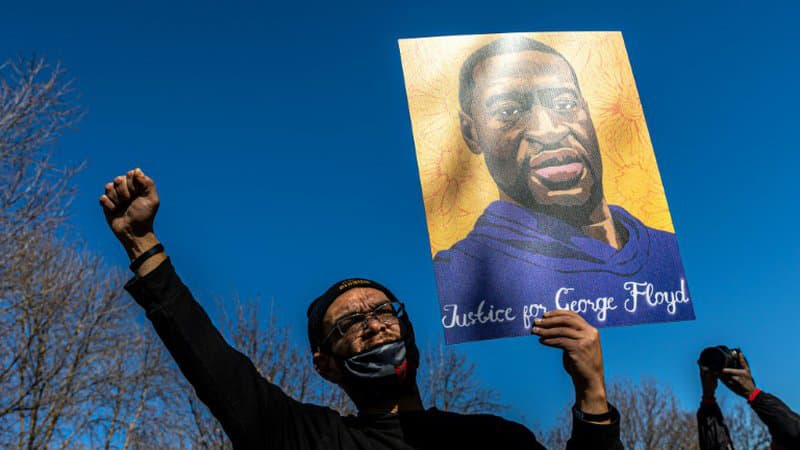 Un-manifestant-brandit-un-portrait-de-George-Floyd-a-St-Paul-ville-jumelle-de-Minneapolis-le-6-mars-2021-1006668
